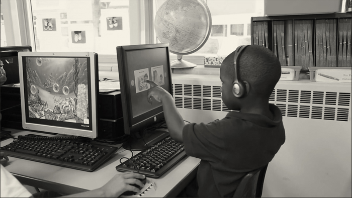 Boy playing on computer in classroom