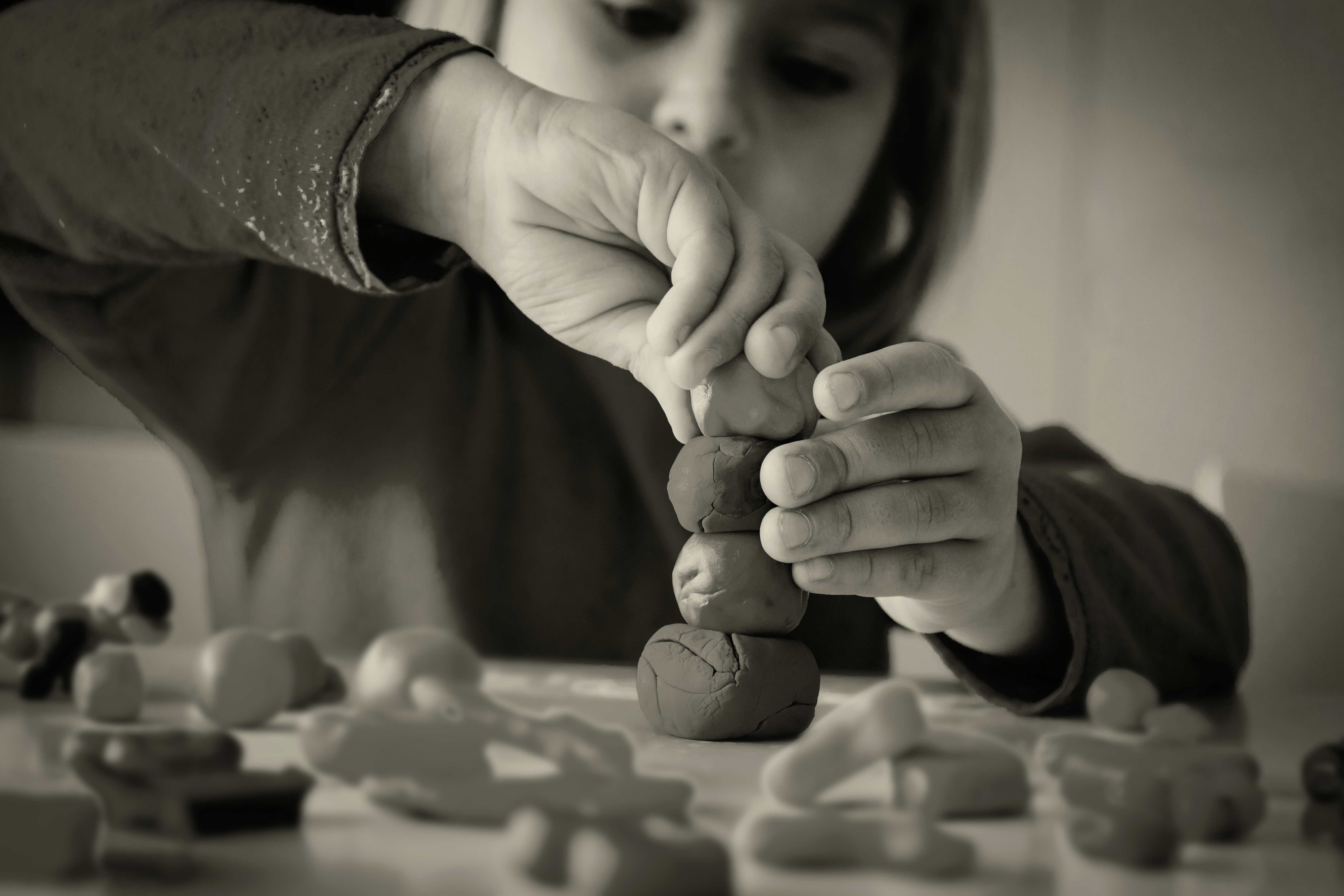 Child building a figure out of clay