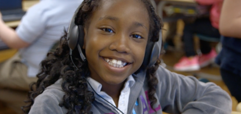 Imagine Learning student smiling with headphones