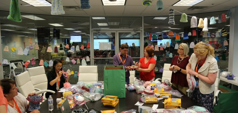 Imagine Learning employees knit hats during Vision Conference